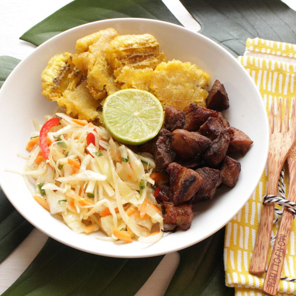 Assiette de pikliz ( mélange de chou et de carottes épicé), griot de porc, bananes plantains frites