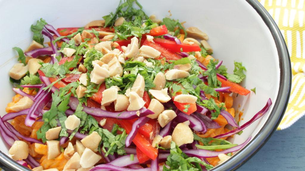 Bol de salade de nouilles à la sauce sriracha et beurre de cacahuètes, lamelles de poivrons et de chou, coriandre ciselée