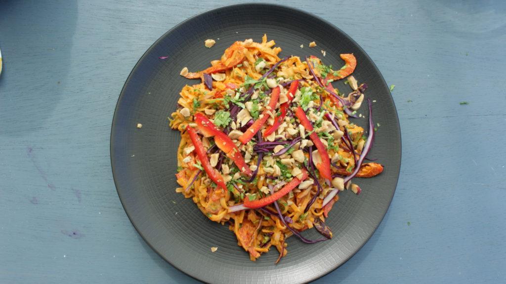 Assiette de salade de nouilles épicée au beurre de cacahuètes et poivrons rouges